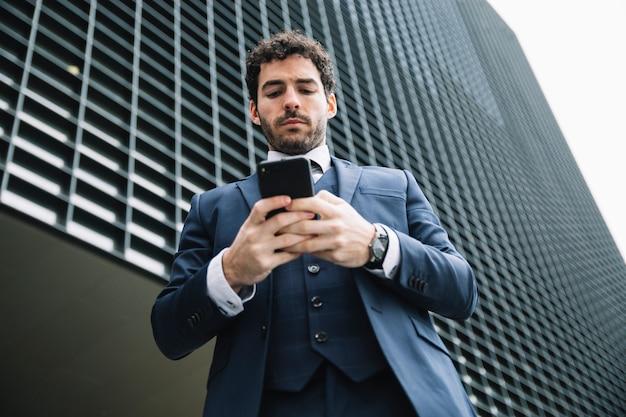 Homme d'affaires moderne utilisant un smartphone à l'extérieur Photo gratuit
