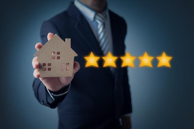 Homme d'affaires montrant le classement par étoiles ou objectif sur bleu foncé Photo Premium