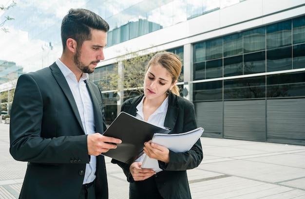 Homme d'affaires montrant des documents à sa collègue debout devant le bureau Photo gratuit