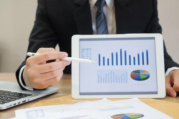 Homme d'affaires montrent les données de tableau de bord sur la tablette et la main pointant pour expliquer la statistique Photo Premium