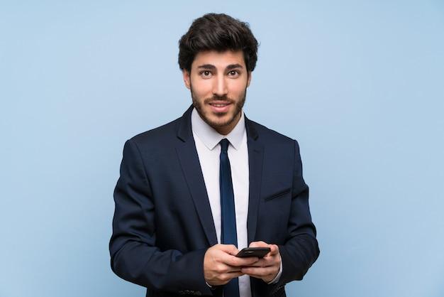Homme d'affaires sur un mur bleu isolé, envoyant un message avec le téléphone portable Photo Premium