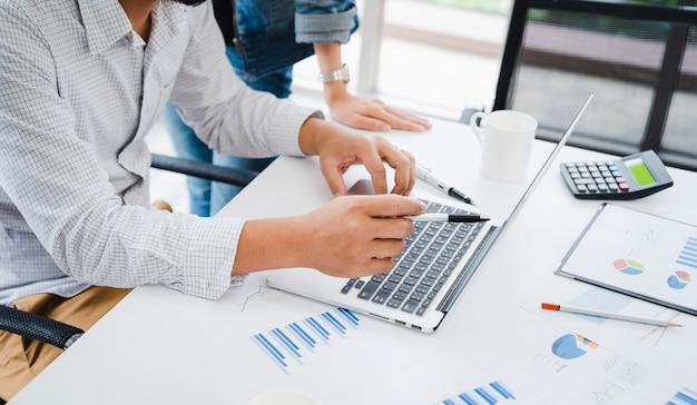 Homme D'affaires Occasionnel Discuter Du Plan Marketing Sur Ordinateur Portable Pour Faire équipe Avec Du Papier Graphique Sur Table Photo Premium