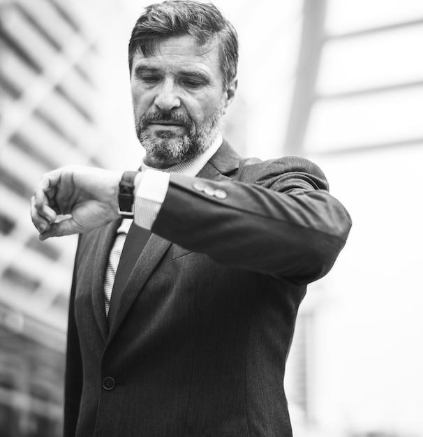 Homme d'affaires occupé vérifiant sa montre Photo gratuit