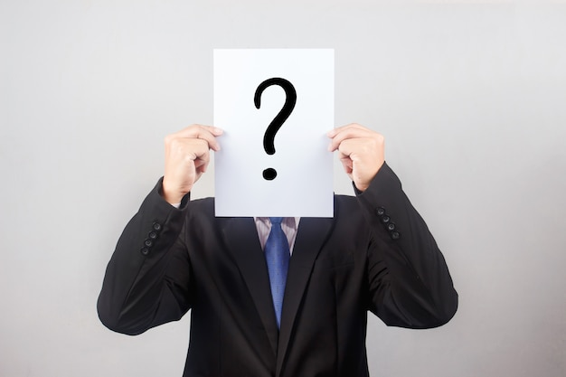 Homme d'affaires avec le papier de la question sur fond gris Photo Premium