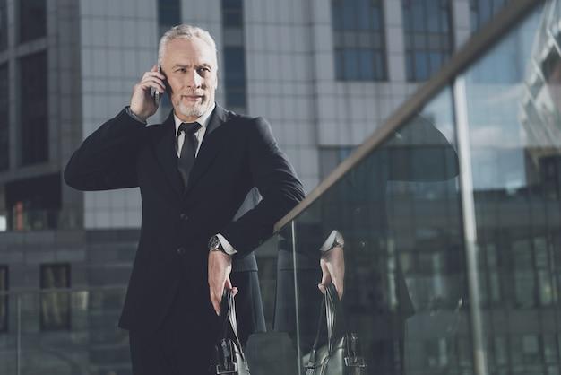 Homme d'affaires parle au téléphone mobile Photo Premium