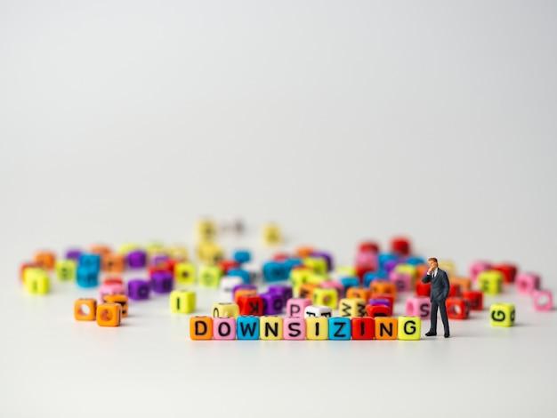 Homme d'affaires de personnage miniature en costume bleu foncé, debout à l'arrière d'un alphabet coloré de réduction des effectifs Photo Premium
