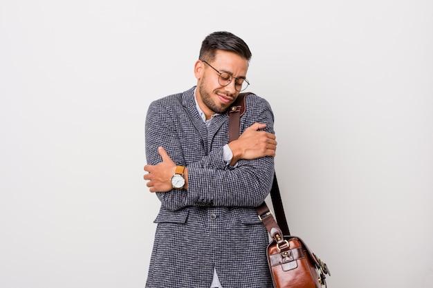 Homme d'affaires philippin de jeunes entrepreneurs contre un mur blanc étreint, souriant insouciant et heureux. Photo Premium