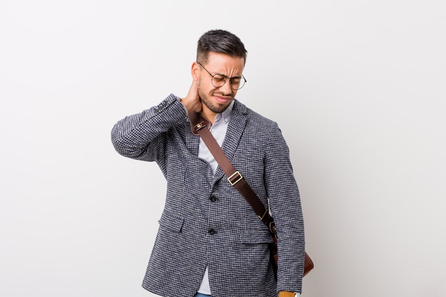 Homme d'affaires philippin de jeunes entrepreneurs contre un mur blanc souffrant de douleurs au cou due à un style de vie sédentaire. Photo Premium