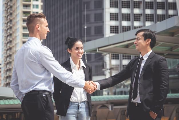 Homme d'affaires avec poignée de main avec partenaire et femme acclamant Photo Premium
