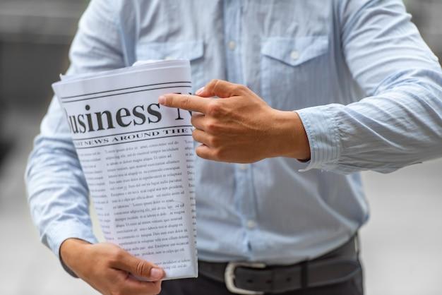 Homme d'affaires pointe son journal pour lire des nouvelles dans les affaires. Photo Premium