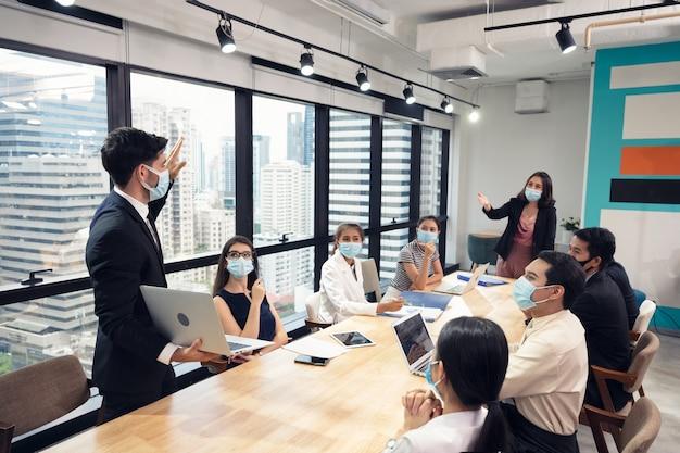Homme D'affaires Portant Un Masque Facial Avec Présentation Du Plan D'affaires Sur Ordinateur Portable Photo Premium