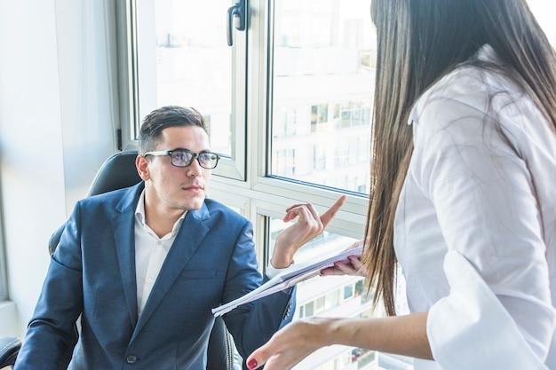 Homme d'affaires posant des questions à la femme d'affaires au bureau Photo gratuit