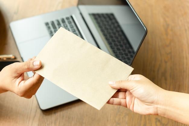 Homme d'affaires prenant de l'argent de pot-de-vin dans une enveloppe brune du concept de corruption partenaire. Photo Premium