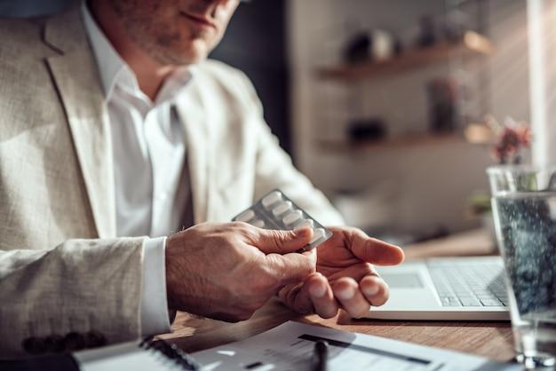Homme d'affaires prenant des pilules médicales au bureau Photo Premium