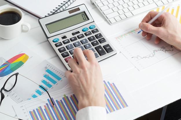 Homme d'affaires prépare un rapport financier en utilisant une calculatrice. Photo Premium