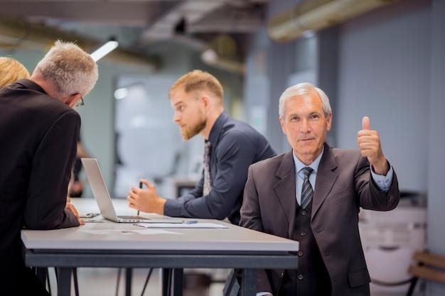 Homme affaires, projection, pouce haut, signe, séance, devant, son, équipe, discuter, bureau Photo gratuit