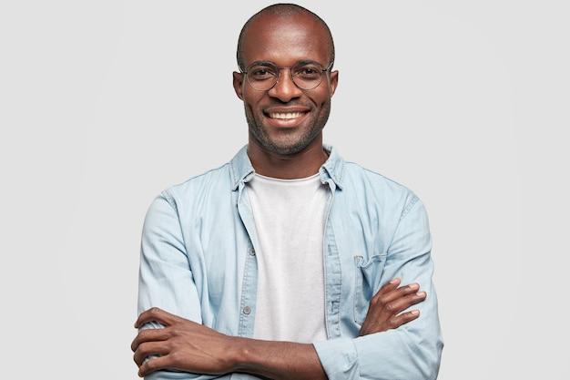 Homme D'affaires Prospère Garde Les Mains Croisées, A Une Expression Satisfaite Photo gratuit