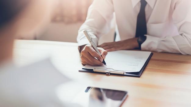 Un homme d'affaires qui écrit un formulaire soumet un cv à son employeur pour examiner sa candidature. Photo Premium