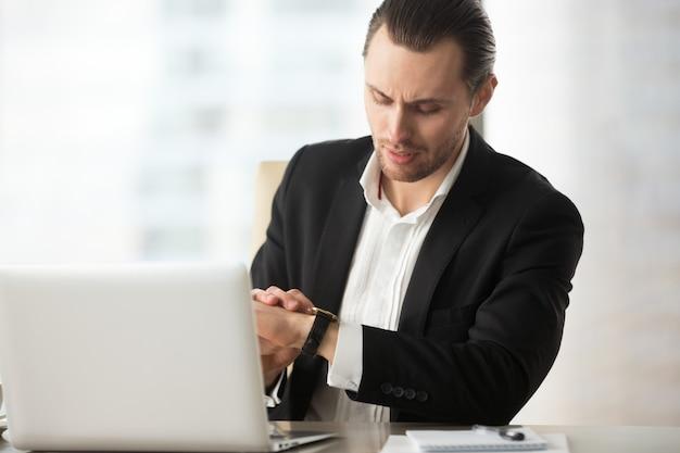 Homme d'affaires en regardant montre-bracelet au bureau de travail au bureau. Photo gratuit