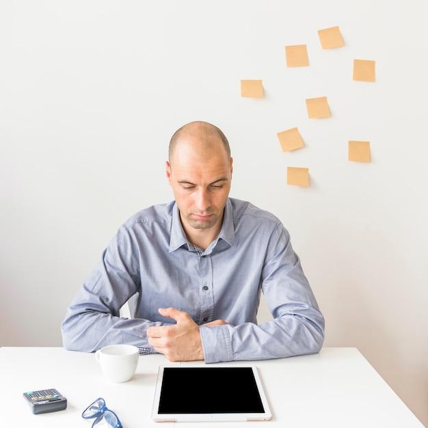 Homme d'affaires en regardant une tablette numérique avec écran blanc Photo gratuit