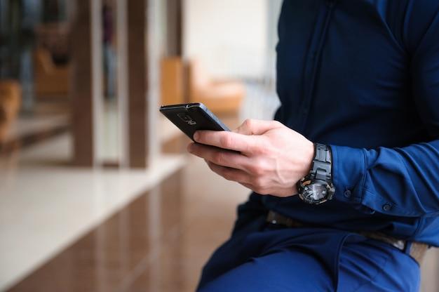 Homme d'affaires en regardant à travers le téléphone par la fenêtre Photo Premium