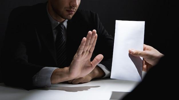 Homme d'affaires rejetant de l'argent dans une enveloppe blanche offerte par son partenaire dans l'ombre Photo Premium