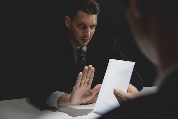 Homme d'affaires rejetant de l'argent dans une enveloppe blanche offerte par son partenaire Photo Premium