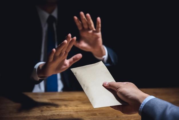 Homme d'affaires rejetant l'argent dans l'enveloppe, concept anti-corruption Photo Premium