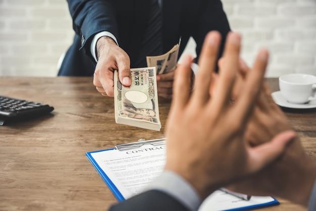 Homme d'affaires rejetant l'argent, en devise du yen japonais, de sa part Photo Premium