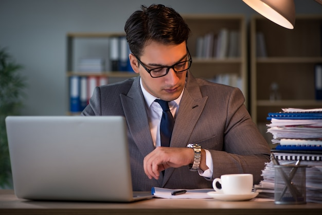 Homme d'affaires restant au bureau pendant de longues heures Photo Premium