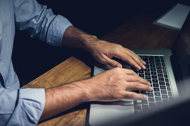 Homme d'affaires restant des heures supplémentaires tard dans la nuit, travaillant avec un ordinateur portable Photo Premium
