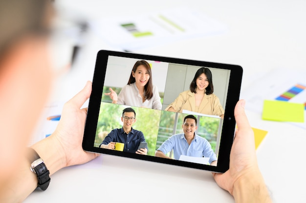 L'homme D'affaires A Une Réunion Avec Des Collègues Asain Sur Le Plan De La Vidéoconférence Via Tablette Photo Premium