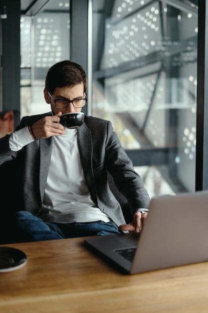 Homme D'affaires Réussi Travaillant Sur Ordinateur Portable Tout En Buvant Du Café Photo gratuit