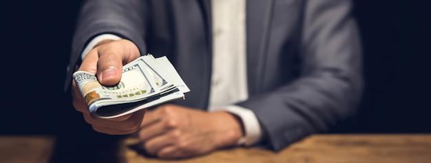 Homme d'affaires riche détenant et donnant de l'argent en dollars américains dans une pièce privée sombre Photo Premium