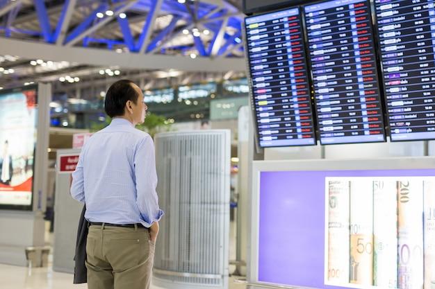 Homme d'affaires avec sac à dos à l'aéroport regarder les horaires de vol. Photo Premium