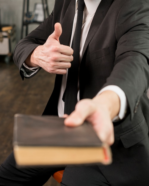 Homme d'affaires satisfait donnant un livre montrant le pouce vers le haut Photo gratuit