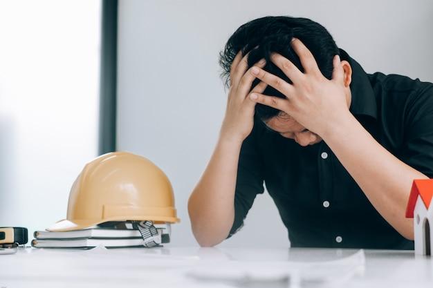 Homme d'affaires se sentir la tête dans leur coeur alors qu'ils travaillaient au bureau, concept médical Photo Premium