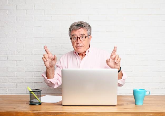 Homme d'affaires senior croise les doigts en quête de chance, avec une expression pleine d'espoir, empressée et excitée. Photo Premium