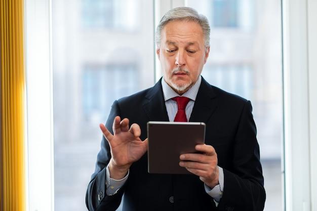 Homme D'affaires Senior Debout Et Tenant Une Tablette Numérique à La Main Photo Premium