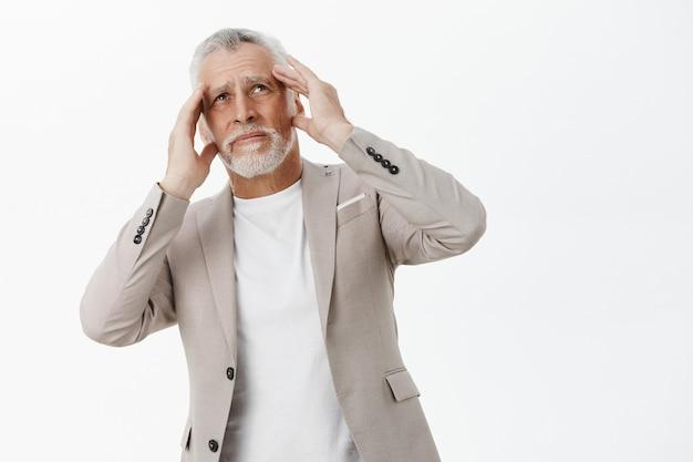 Homme D'affaires Senior Mécontent, Tenant Les Mains Sur La Tête Et L'air Dérangé, Se Plaignant De Bruit Fort Photo gratuit