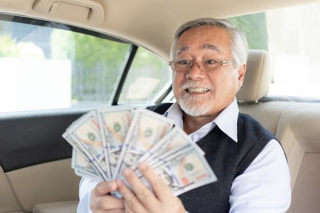 Homme d'affaires senior riche tenant des billets d'un dollar américain en argent sur sa voiture Photo Premium