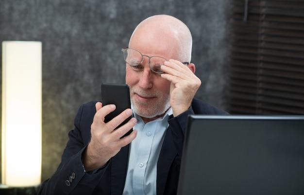 Homme d'affaires senior utilisant un smartphone, il a des difficultés et des problèmes de vision Photo Premium