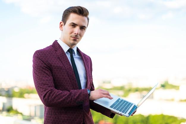Homme d'affaires sérieux en costume rouge et chemise avec cravate se tenir sur le toit avec ordinateur portable Photo Premium