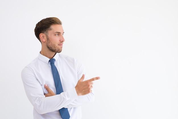 Homme d'affaires sérieux pointant du doigt de côté Photo gratuit