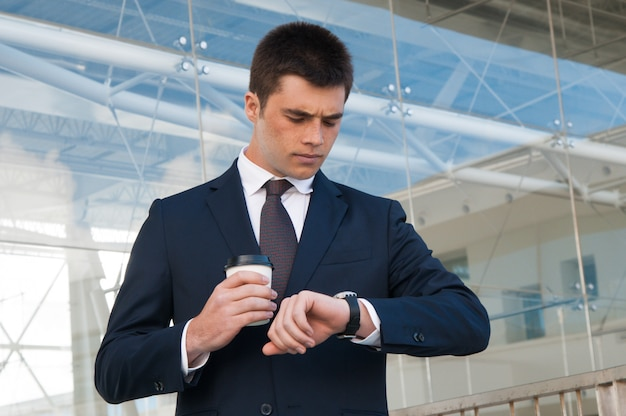 Homme d'affaires sérieux vérifiant l'heure sur la montre à l'extérieur Photo gratuit