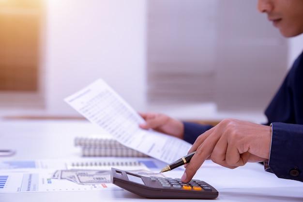 Un homme d'affaires de sexe masculin reste longtemps à gagner de l'argent. Photo Premium