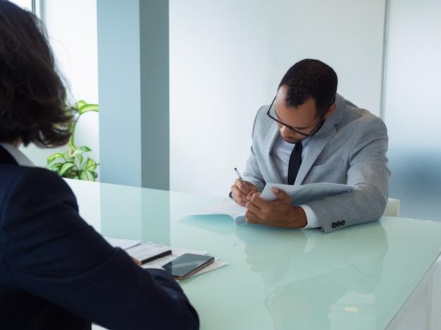Homme d'affaires signant un accord lors d'une réunion Photo gratuit