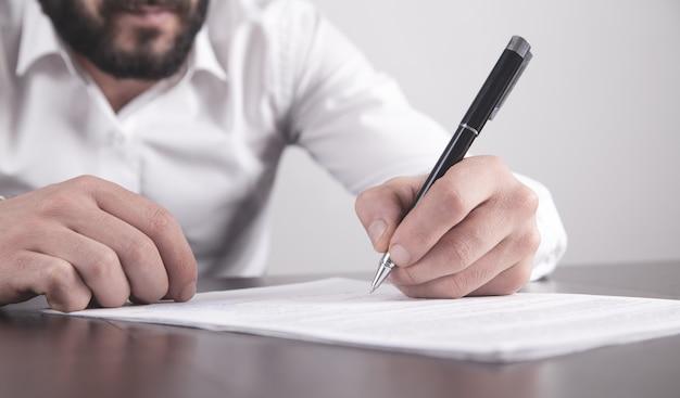 Homme D'affaires Signant Un Contrat Au Bureau. Photo Premium