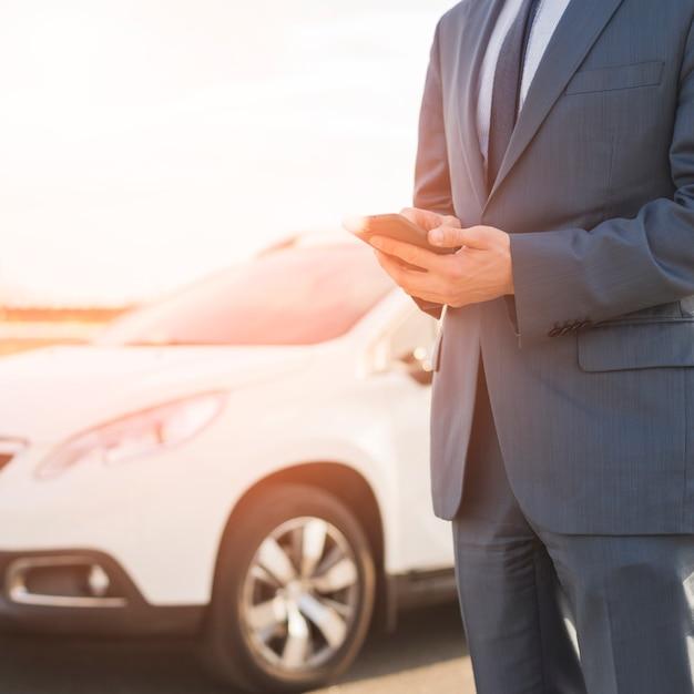 Homme d'affaires avec un smartphone devant la voiture Photo gratuit