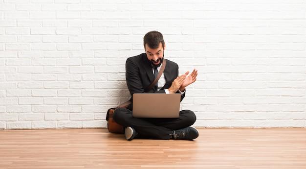 Homme d'affaires avec son ordinateur portable assis sur le sol, applaudissant après la présentation à une conférence Photo Premium